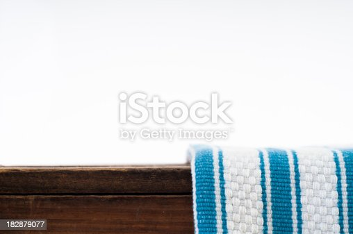 White and blue striped dish cloth on brown wood