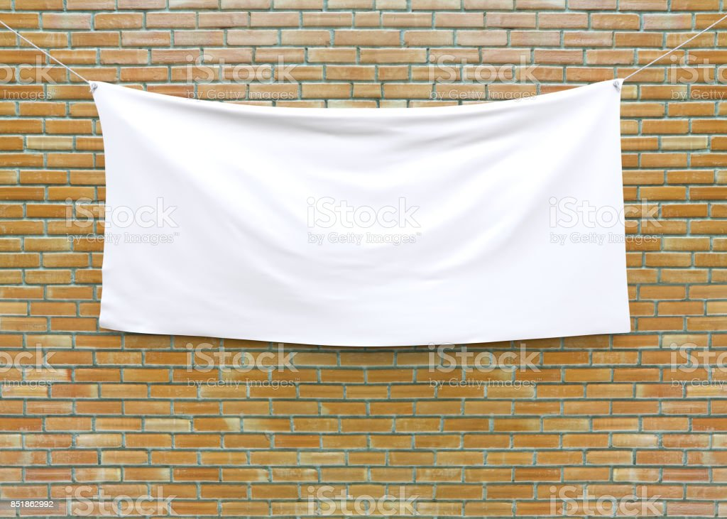 Cloth banner hanging on brick wall. stock photo