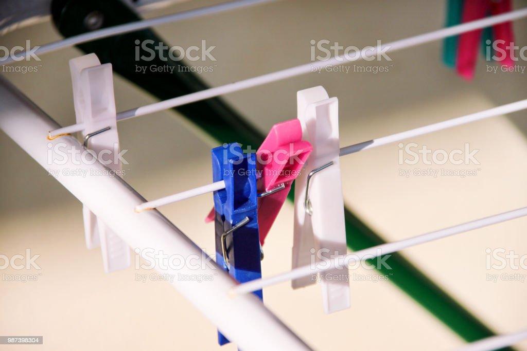 Prendedores de roupa de pano na cremalheira de secagem, foco seletivo. Prendedores de plástico coloridos no varal. Um monte de grampos de pano de lã multicolorido anexado a corda. Prendedor de plástico cor pendurado em um fio. - foto de acervo
