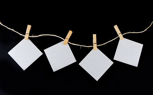 Clothe pin on the rope with paper note on the black background