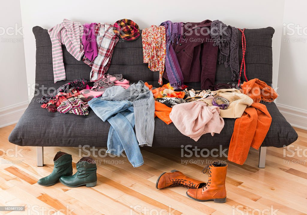 Clothes and boots placed haphazard over floor and sofa stock photo