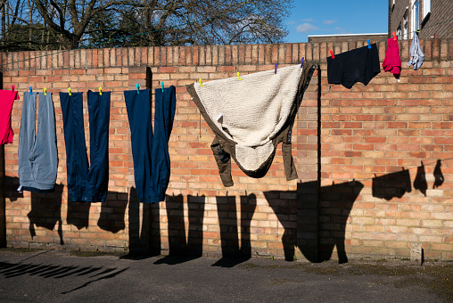 Clothes drying on a washing line with shadows on a wall