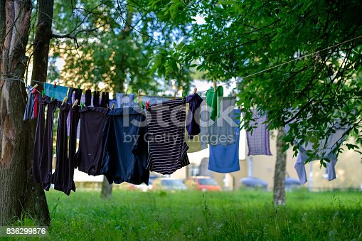 Clothes drying on the laundry line between green trees on fresh air in summer