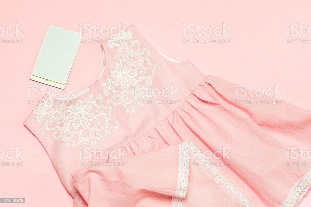 Kleidung für kleines Mädchen auf einem rosa Hintergrund. Textfreiraum Lizenzfreies stock-foto