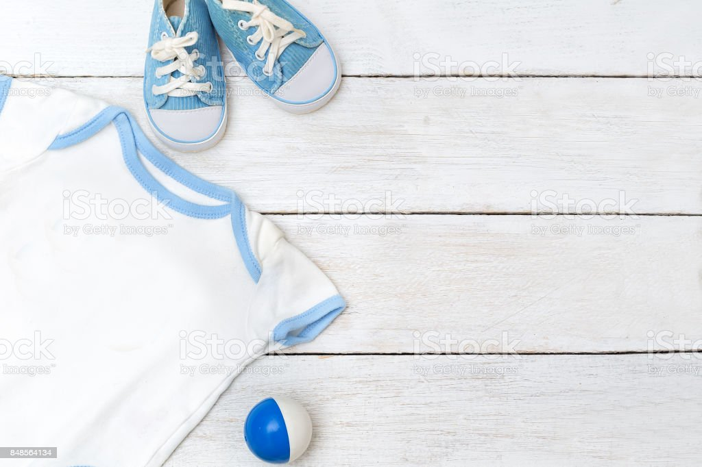 clothes for the kid and shoes on a white wooden background stock photo