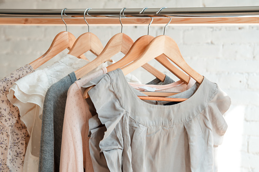 Female clothes on clothing rack. Pastel colors