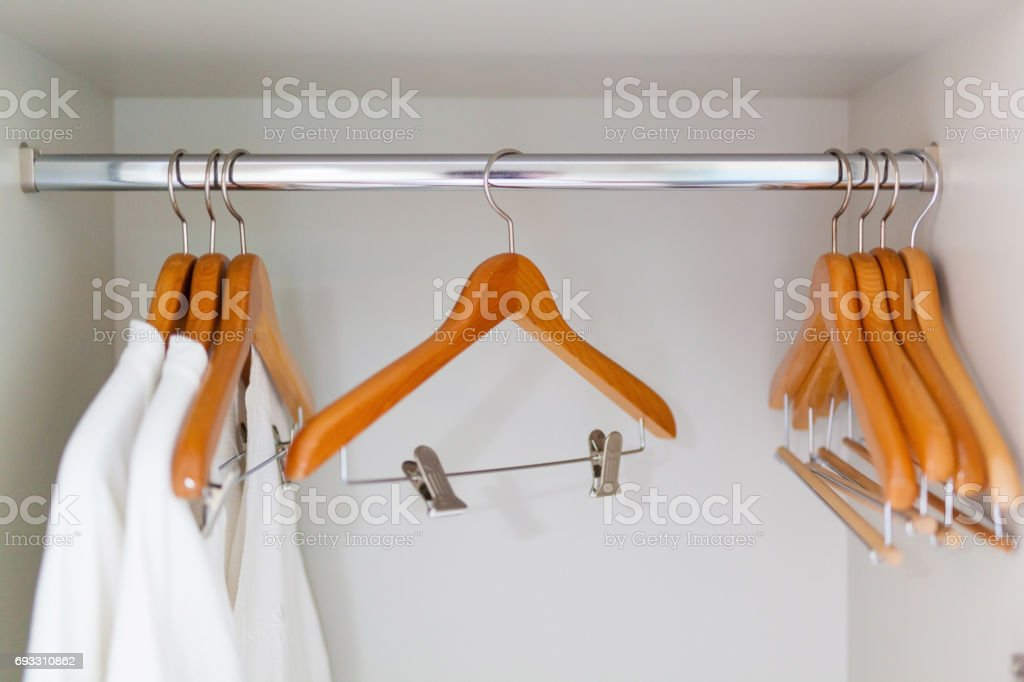 clothes hangers and white shower gown in clothes chest stock photo
