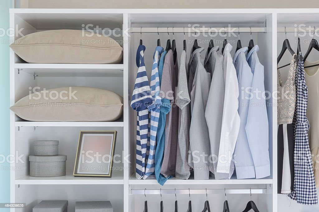 clothes hanging in white wardrobe stock photo