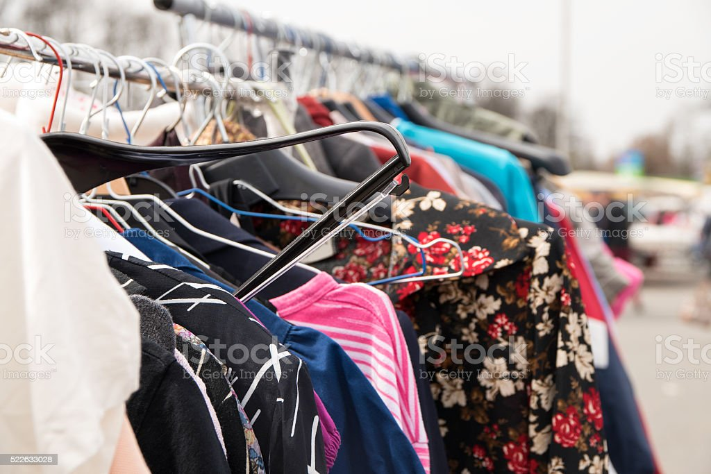 clothes hanging on a rack for sale, flea market stock photo