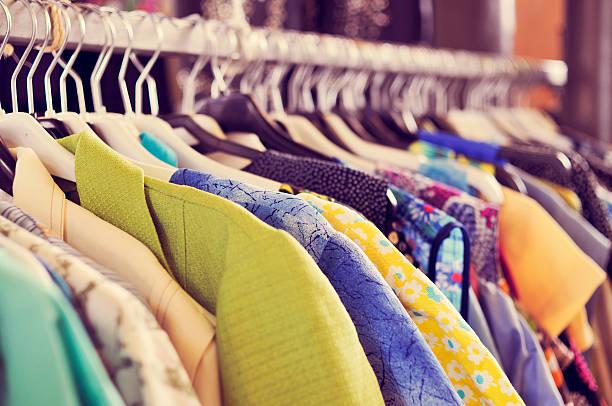 kleidung hängen auf einem ständer in einem flohmarkt - kleider günstig kaufen stock-fotos und bilder