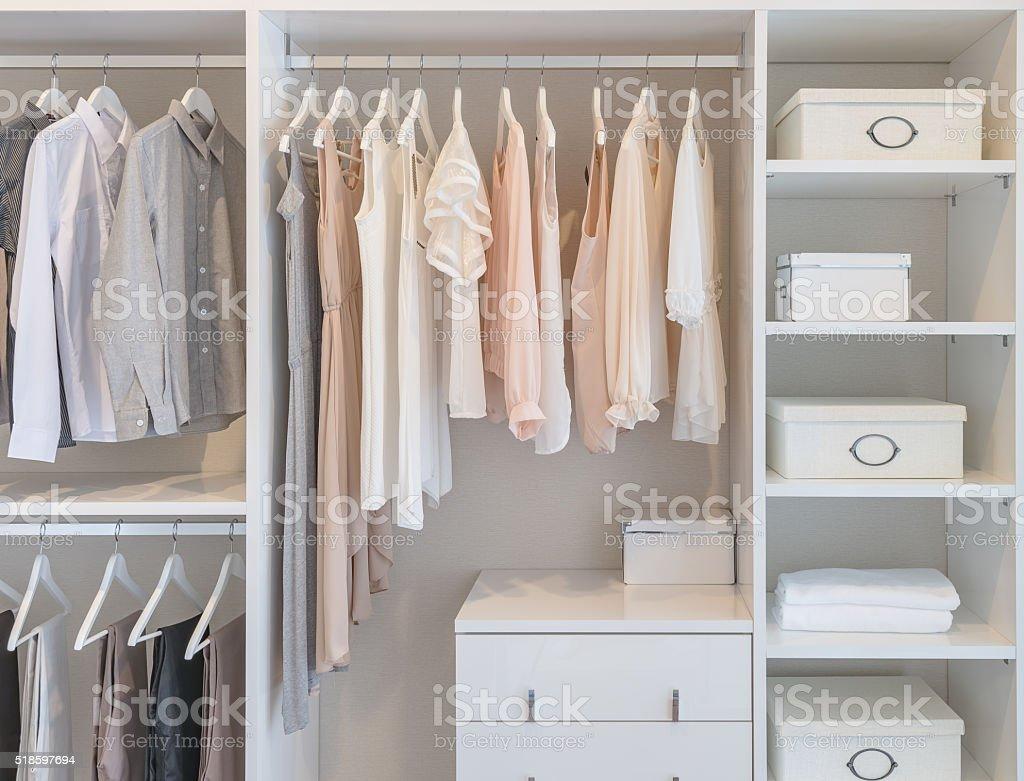 Clothes Hanging On Rail In White Wardrobe Stock Photo