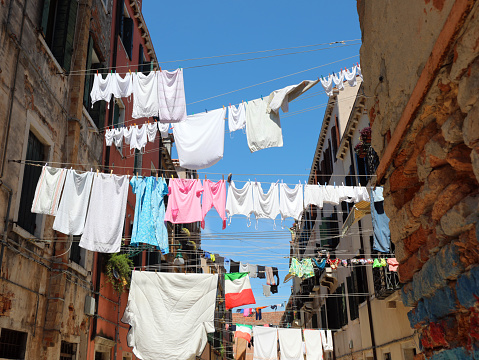 clothes hanging out drying in the sun in the narrow street of the typical Italian city