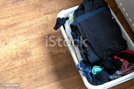 460589747 istock photo clothes in a full laundry basket on a laminate floor, top view 1199310330