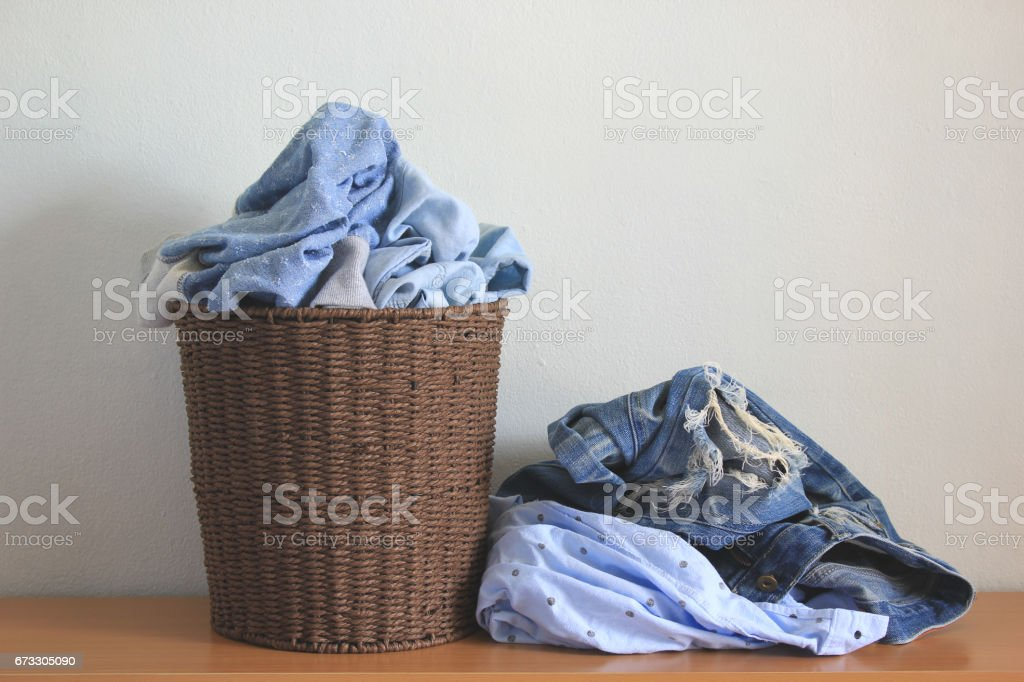 Clothes in a laundry wooden basket on wood table royalty-free stock photo