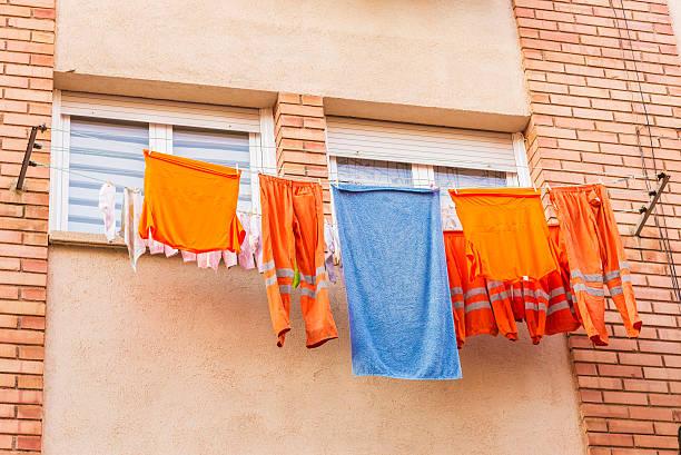 clothes of a worker hanging from a clothesline to dry - orangenscheiben trocknen stock-fotos und bilder