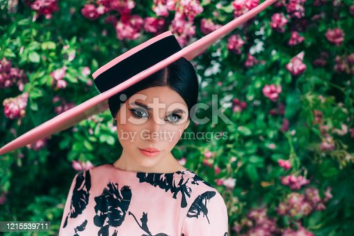 Clothes Old retro woman style. lady Pink hat wide brimmed. Natural cosmetics concept, holiday cat eyes liner makeup, girl cute face lips. Spring blooming garden green rose bushes. Fashion 50s 60s