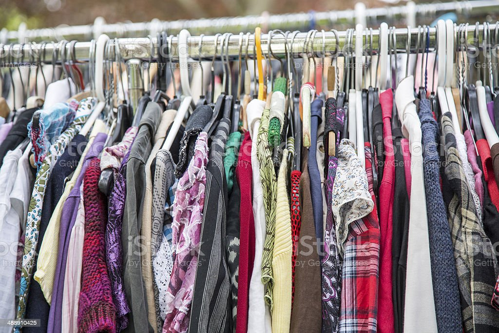 clothes on a rack in a flea market stock photo