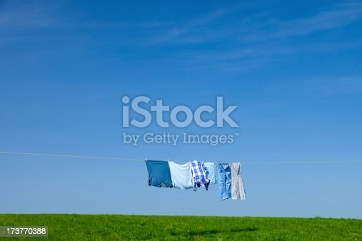 Clothes drying on a washing line stretched across a field in the Summer.