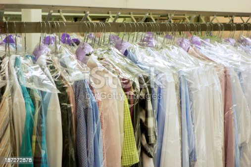 close up of dry cleaned clothes on a hanger. horizontal shot of various pieces of garments in a dry cleaning. The garments are protected by a transparent plastic foil until the customer picks the clothes up. There are mostly dry cleaned shirts.