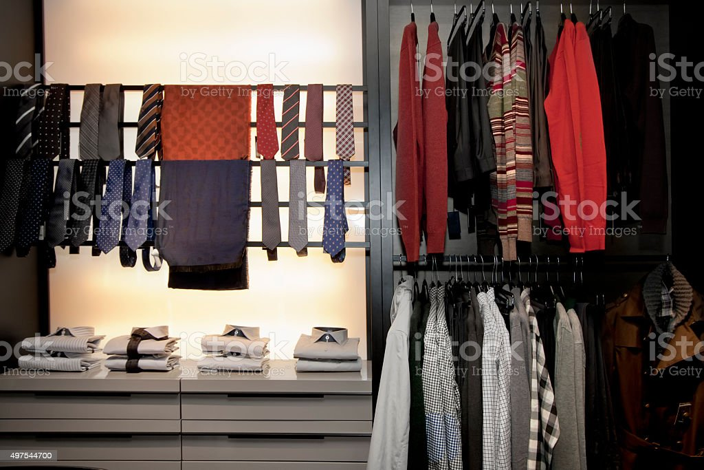 Clothes on hangers and folded on racks. stock photo