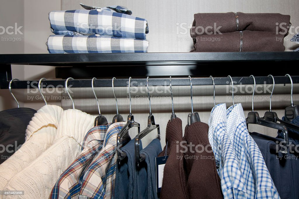 Clothes on hangers and folded on shelf. stock photo