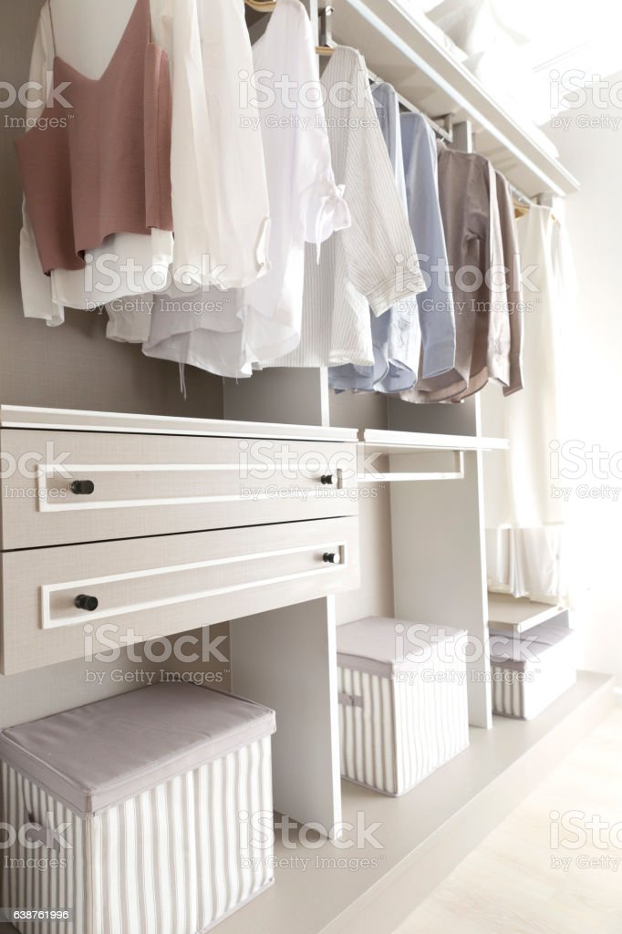 clothes on hangers in wardrobe stock photo
