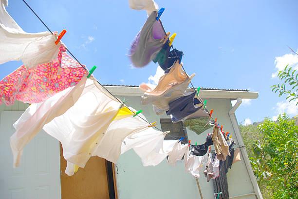 kleider in zeile im freien trocknen im wind und sonne - rustikaler hinterhof stock-fotos und bilder