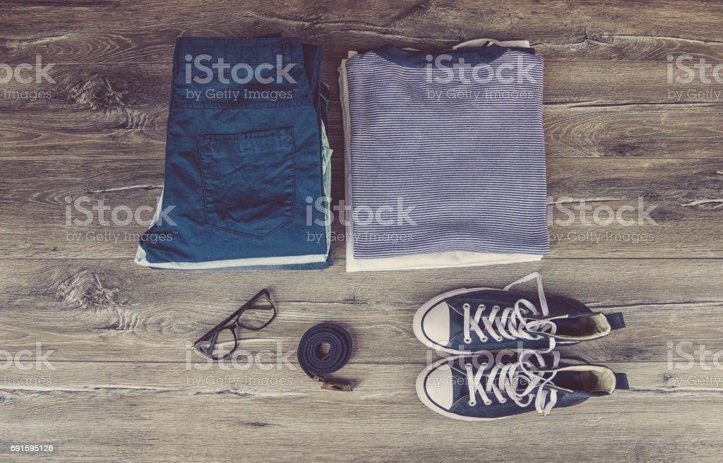clothes, personal staff and objects concept - close up of folded shirts, pants and shoes on table at home over stock photo