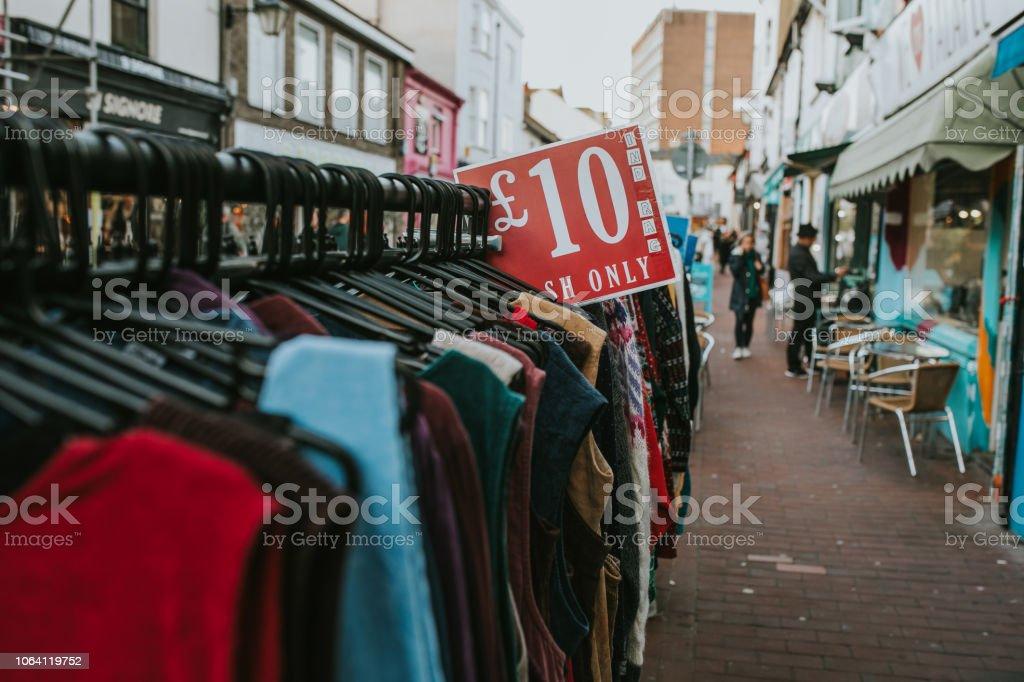 Estante de la ropa de una tienda vintage con jerseys y abrigos. - foto de stock
