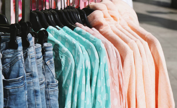 clothes rack with pastel-colored spring fashion hanging outside store stock photo