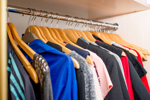 clothes weigh on the shoulders in the closet. Second hand stock photo