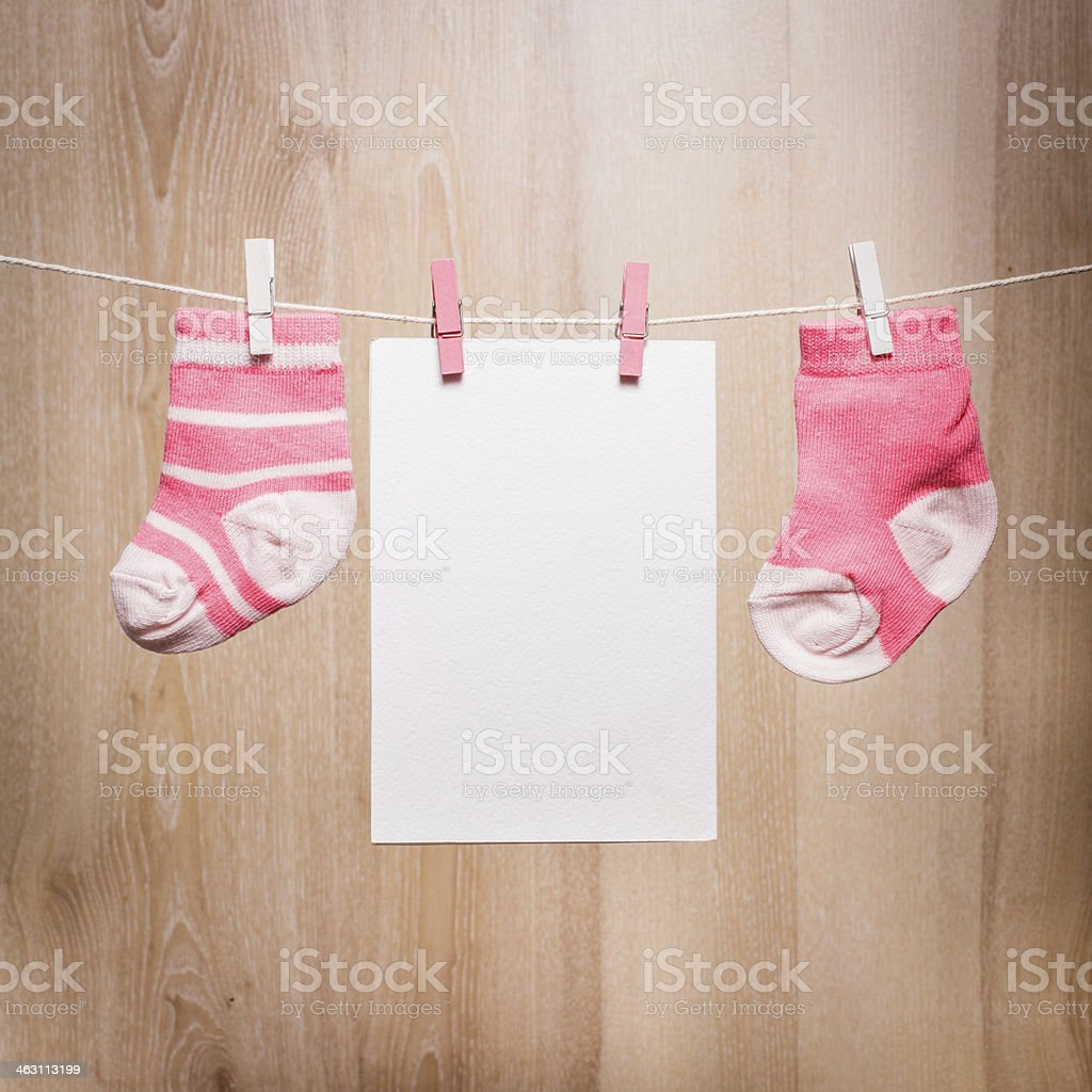 A clothesline holding two baby girl socks and a blank card stock photo