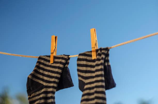 wäscheklammern an einer wäscheleine vor blauem himmel - horizontal gestreiften vorhängen stock-fotos und bilder