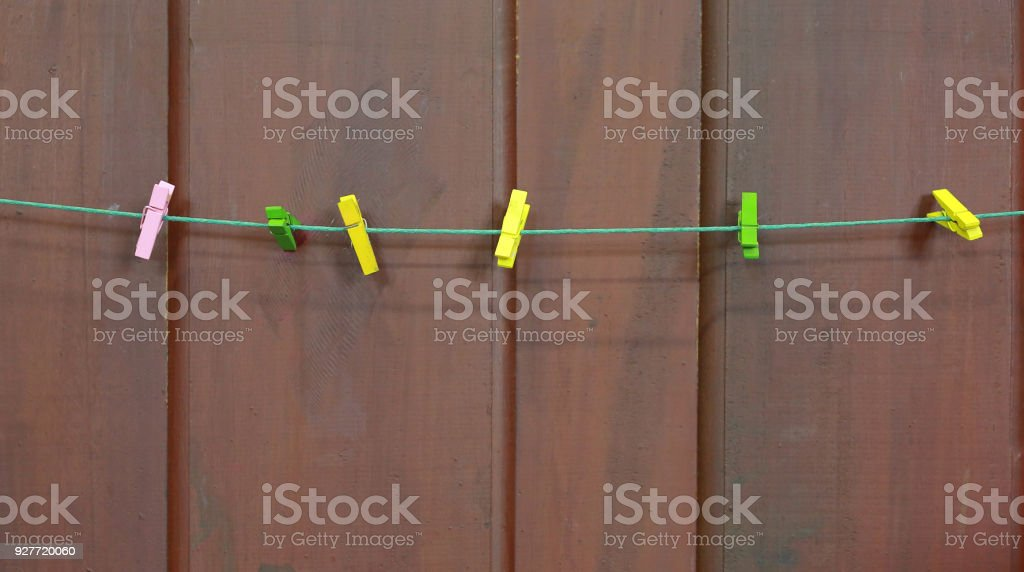 clothespins on rope against brown wood plank wall. stock photo
