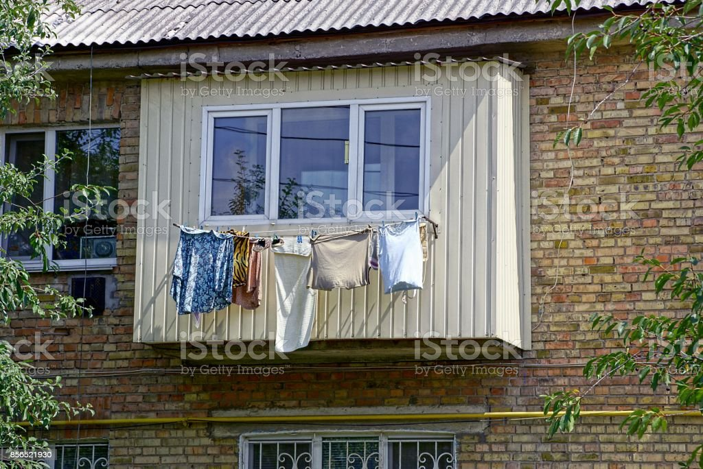 Clothing and laundry dries after washing near the balcony on the wall of the house stock photo