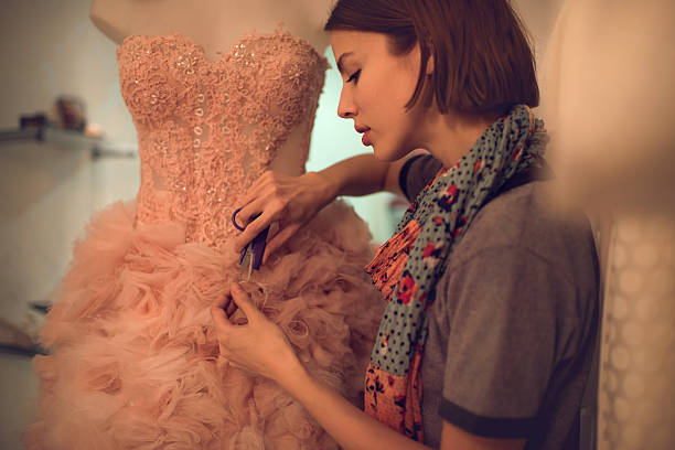 Clothing designer cutting material on a dress in workshop. Female fashion designer working in clothing design studio and using scissors while cutting material on a dress. fashion designer stock pictures, royalty-free photos & images