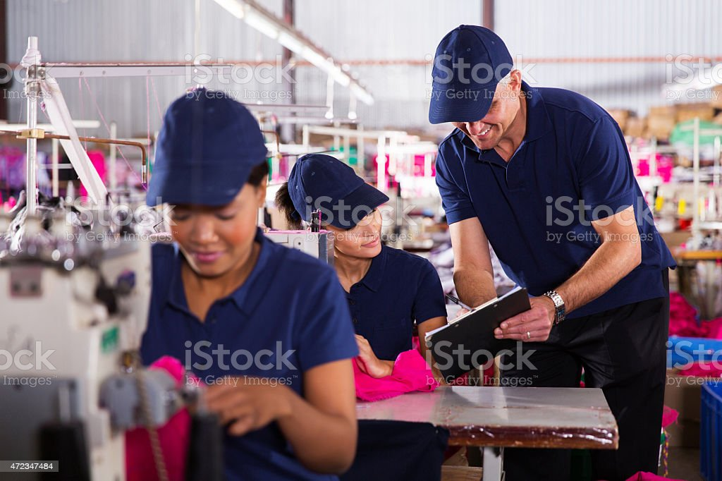 clothing factory foreman explaining work to machinist stock photo