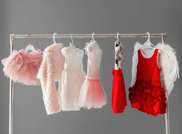Clothing for a little girl on a clothes rack in a wardrobe stock photo