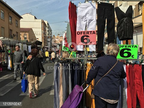 Valencia, Spain - March 12, 2020: People checking clothing for sale at street market in El Cabanyal district. This fair happens every thursday and gathers a lot of people from all over the city