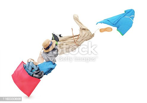 istock Clothing is flying from the paper bag on a white background 1160030658