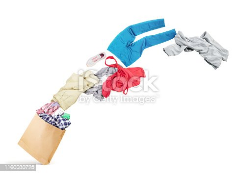 istock Clothing is flying from the paper bag on a white background 1160030725