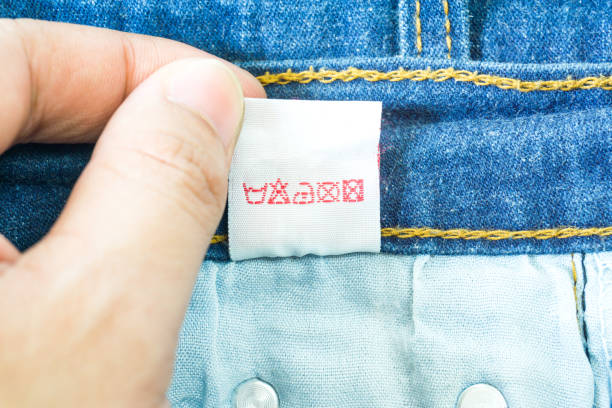 clothing label with laundry instructions, close-up of person reading the clothing label showing washing instructions,clothes, housekeeping concept. - take care of your jeans imagens e fotografias de stock