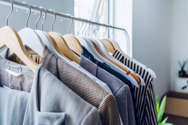 kleidung auf kleiderbügel im modernen shop - uhrenhalter stock-fotos und bilder