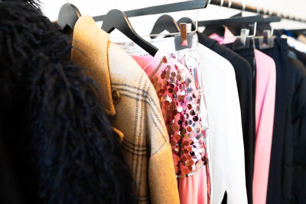 kleidung auf bügel in der trendigen shop-boutique - pailletten shirt stock-fotos und bilder