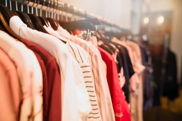 kleidung auf bügel in der trendigen shop-boutique - stoffe berlin stock-fotos und bilder