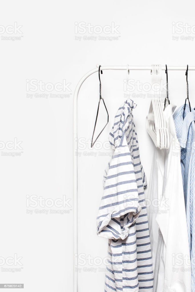 Clothing Rack - Pastel Color Clothes on Cloth Rail over white  Wall Background close up with copyspace. Blue, White and Stripped t-shirts stock photo