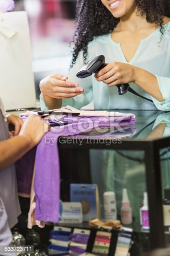 istock Clothing store cashier scanning price tag at checkout 533723711