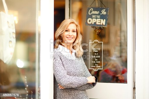 Portrait of attractive clothing store owner standing in her shop entrance. Small shop owner looking at camera and smiling.
