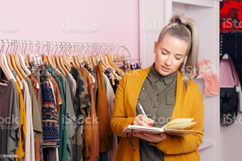 Clothing store owner checking everything its okay. bildbanksfoto