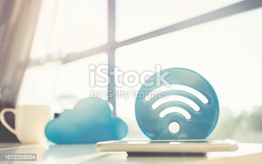 istock Cloud and wifi icons on a coffee table with a mobile phone 1012203054